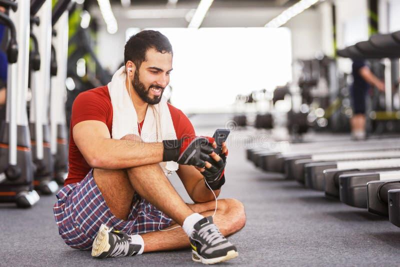 Mens met Smartphone in de Gymnastiek royalty-vrije stock fotografie