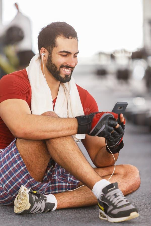 Mens met Smartphone in de Gymnastiek royalty-vrije stock afbeeldingen