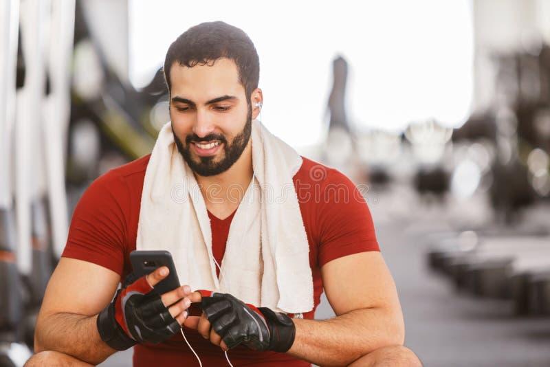 Mens met Smartphone in de Gymnastiek stock fotografie