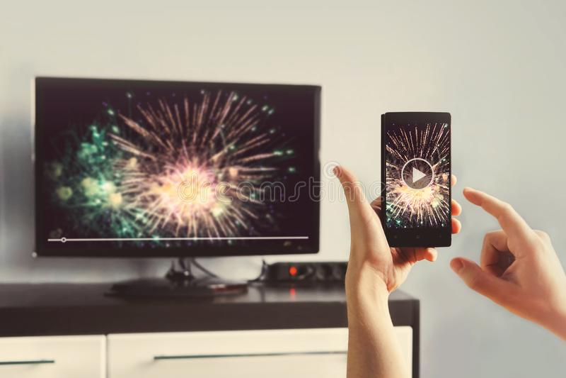 Mens met Smartphone met een TV-het Letten op Video thuis wordt verbonden die stock foto