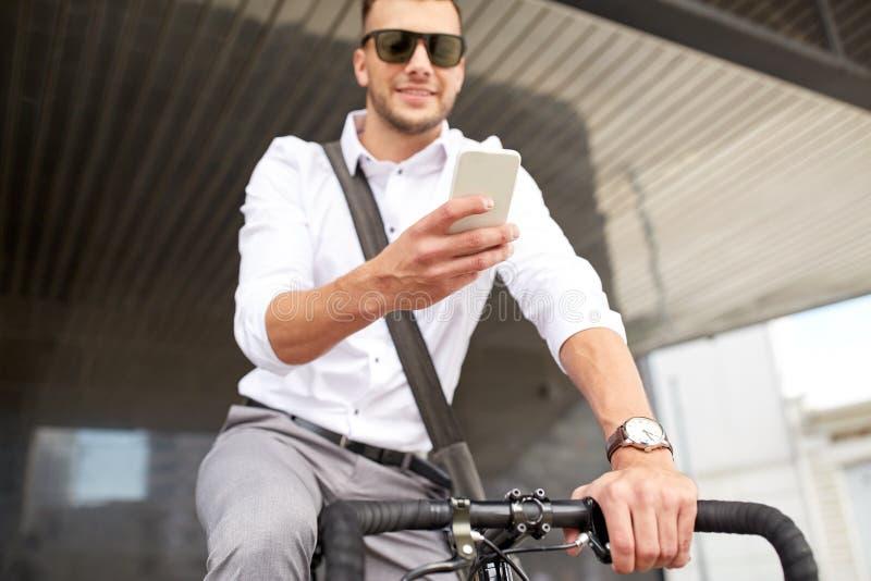 Mens met smartphone en staand vistuigfiets op straat royalty-vrije stock afbeeldingen