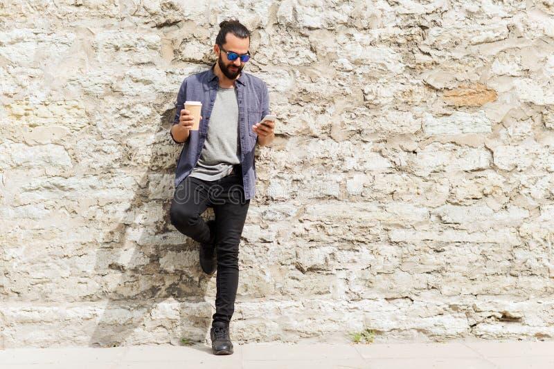 Mens met smartphone het drinken koffie op stadsstraat stock foto's
