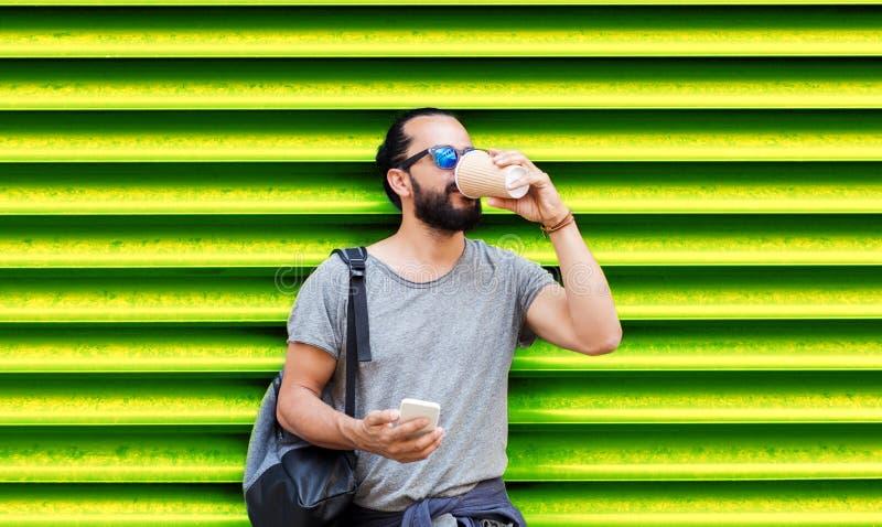 Mens met smartphone het drinken koffie over muur stock afbeelding
