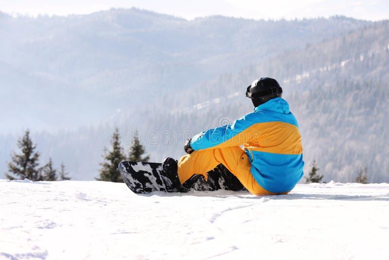 Mens met snowboard die in bergen rusten De winter stock foto's