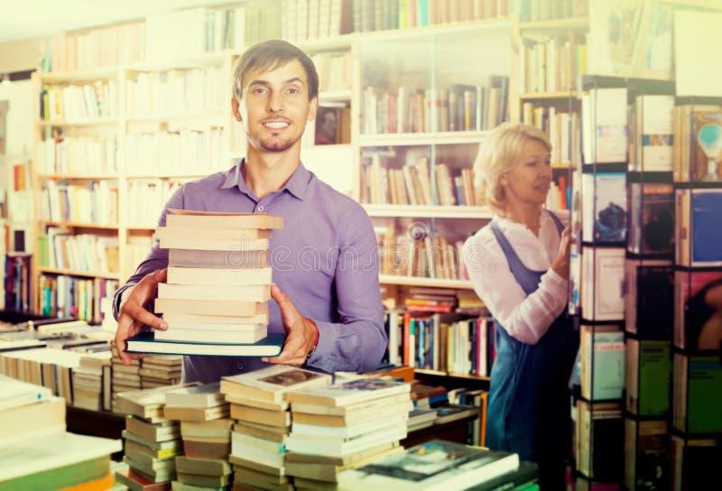 Mens met stapel van boek in boekhandel stock foto
