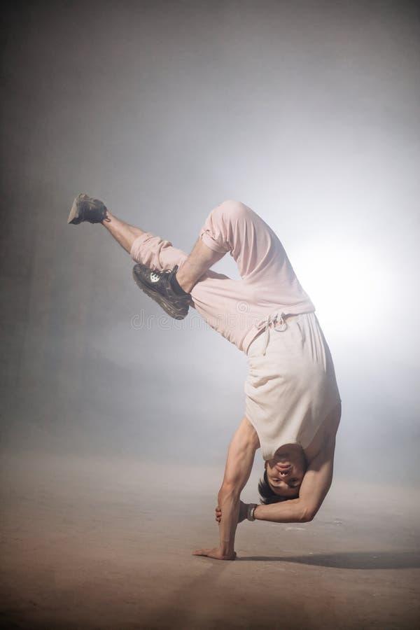 Mens met sterke spieren op wapens die bovenkant - onderaan stunt doen royalty-vrije stock afbeelding