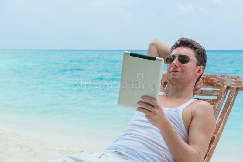 Mens met tablet op strand royalty-vrije stock foto's