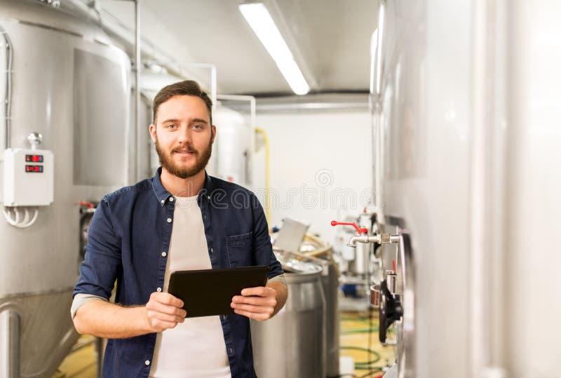 Mens met tabletpc bij ambachtbrouwerij of bierinstallatie stock foto's