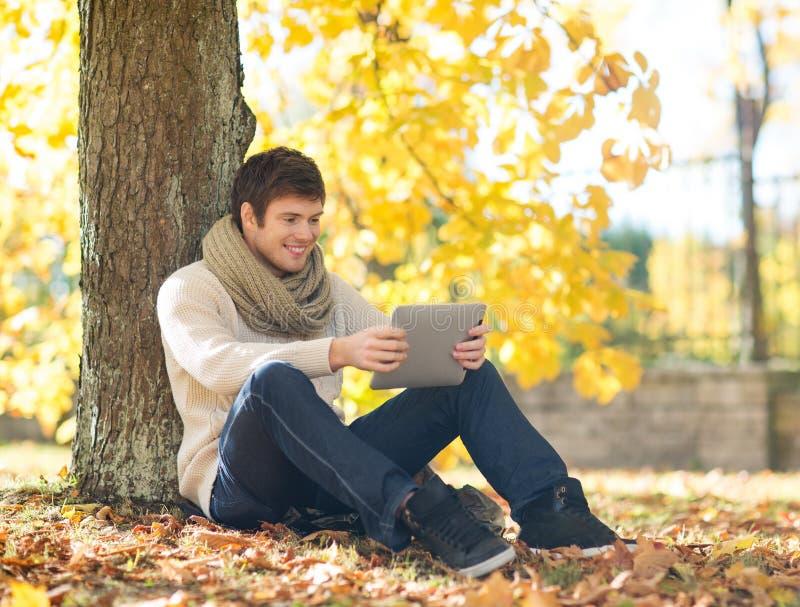Mens met tabletpc in de herfstpark royalty-vrije stock fotografie