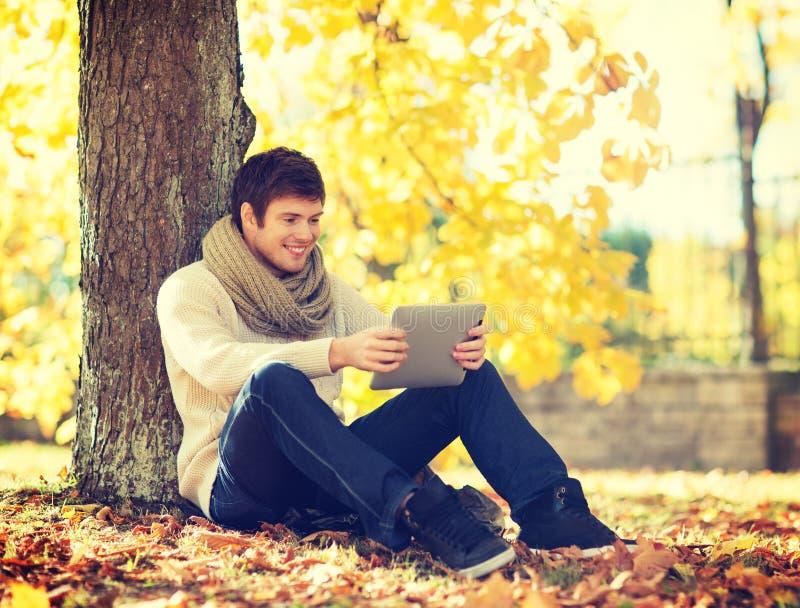 Mens met tabletpc in de herfstpark royalty-vrije stock foto