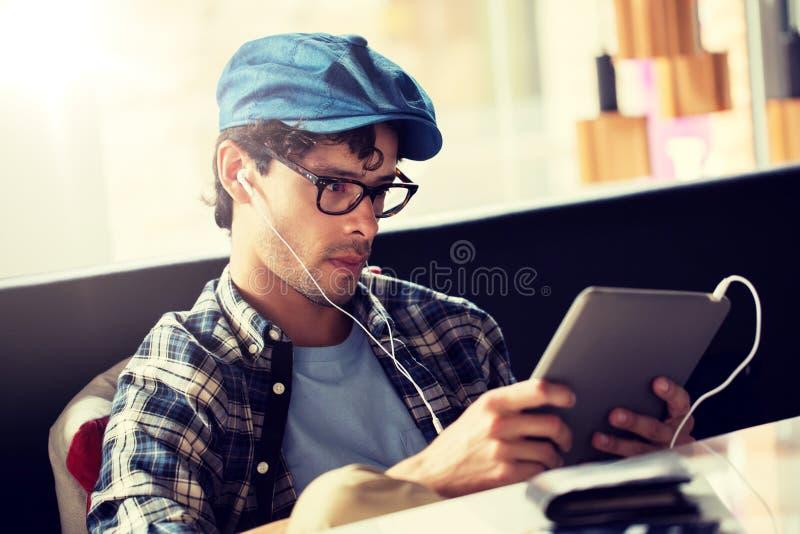 Mens met tabletpc en oortelefoons die bij koffie zitten stock afbeelding