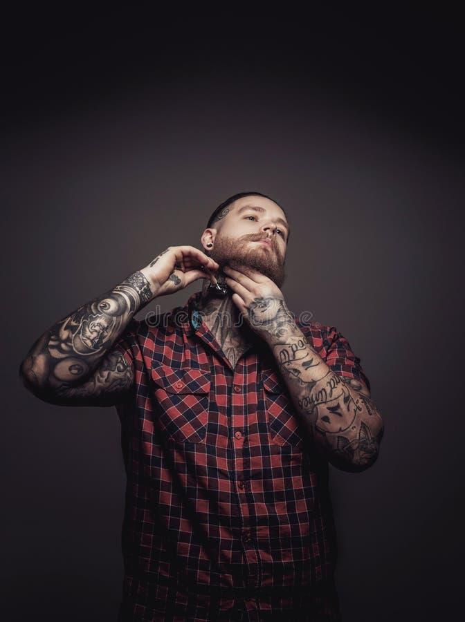 Mens met tattoes en baard stock foto's