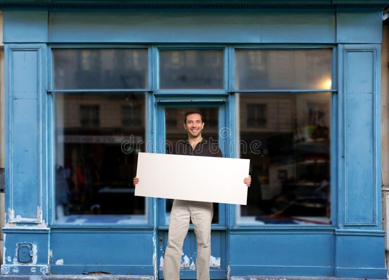 Mens met teken door winkel stock afbeelding