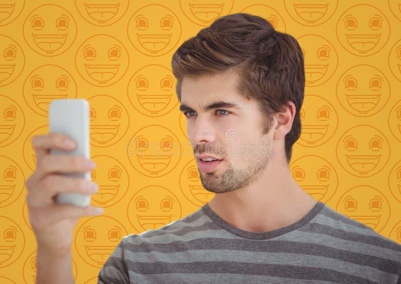 Mens met telefoon tegen geel emojipatroon royalty-vrije stock afbeelding
