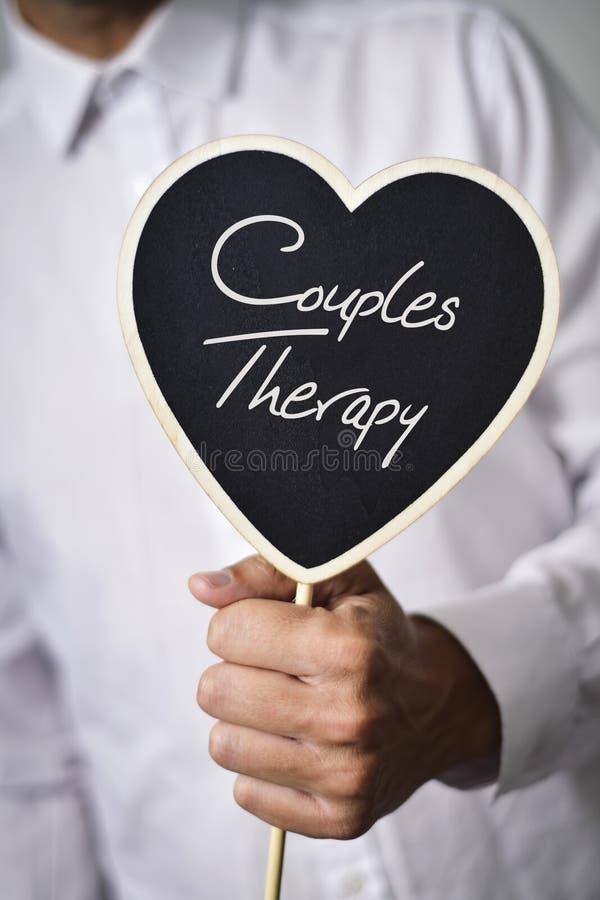 Mens met uithangbord met de therapie van tekstparen stock afbeelding