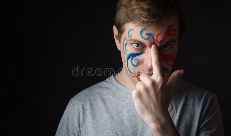 Mens met verf op zijn gezicht stock foto