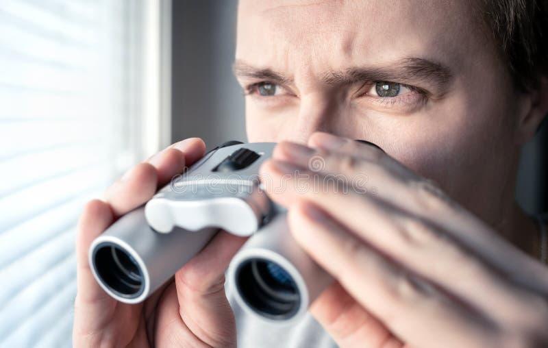 Mens met verrekijkers Privé-detective, agent of onderzoeker die uit het venster kijken Of mens die spioneren onderzoeken stock foto's