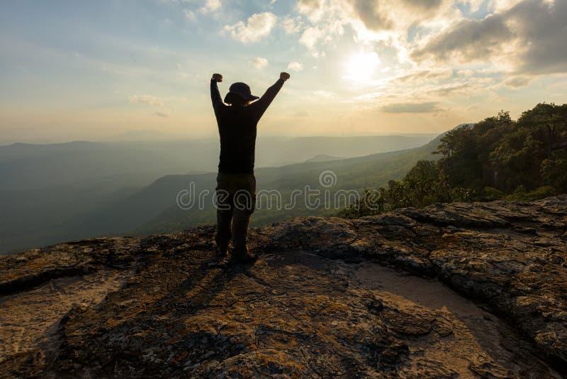 Mens met wapens op de bovenkant van een rots worden opgeheven die stock fotografie