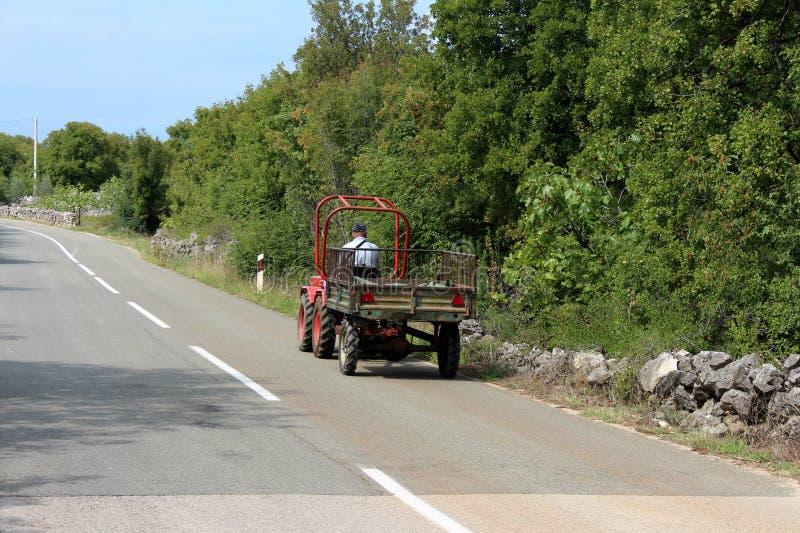 Mens met werkende hoed die kleine tractor met metaalaanhangwagen drijven aan kant van de bedekte weg die met geïmproviseerde stee stock afbeeldingen