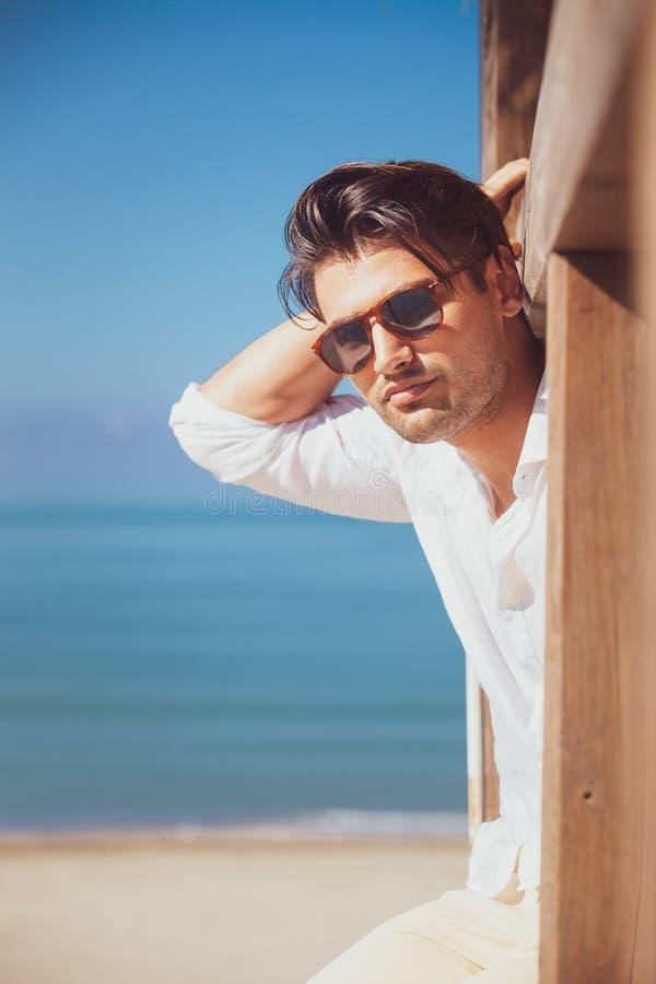 Mens met wit overhemd en zonnebril op strandvakantie die uit eruit zien stock afbeelding