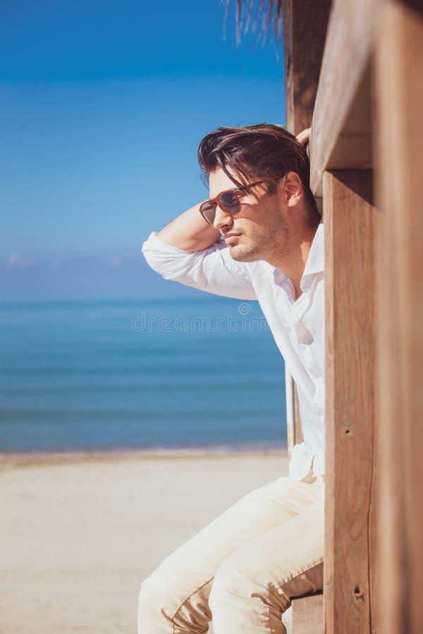 Mens met wit overhemd en zonnebril op strandvakantie die uit eruit zien royalty-vrije stock fotografie
