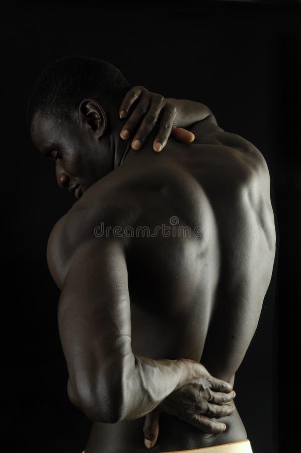 Mens met zijn hand op de rug omdat u pijn, zwarte backg hebt stock fotografie