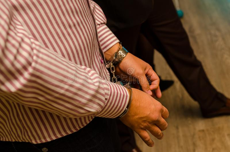 Mens met zijn handen die in misdadig concept de handboeien om:doen royalty-vrije stock foto's