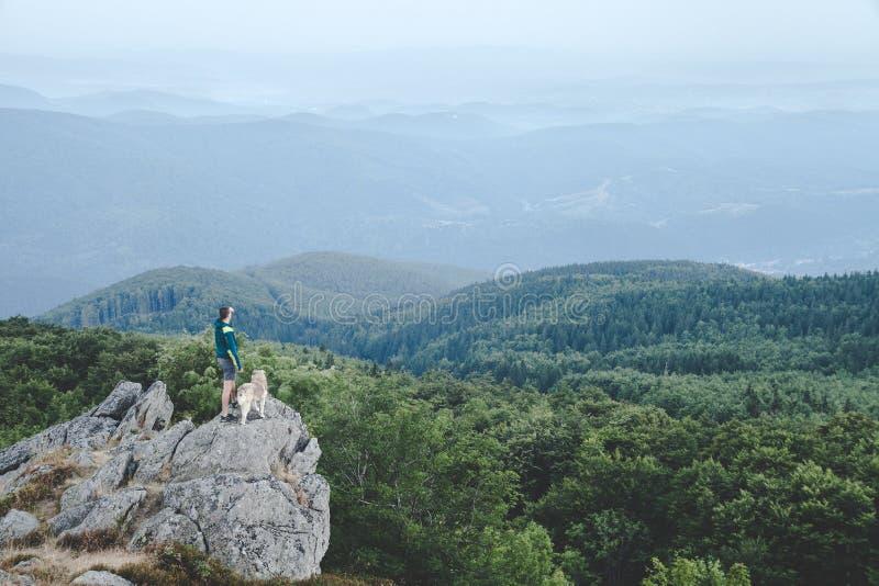 Mens met zijn hond bij de bovenkant van een berg die een mooie mening hebben stock foto's
