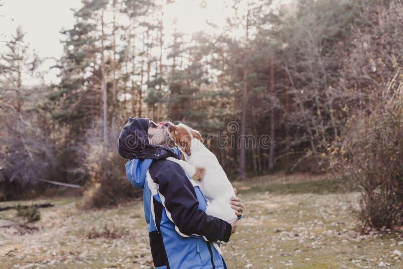 Mens met zijn leuke kleine hond die zich in het bos bij zonsondergang bevinden Gezonde Levensstijl Wandeling Kleine hond die zijn stock fotografie