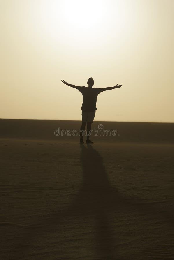 Mens met zijn wapens open in de lucht, in de woestijn stock foto