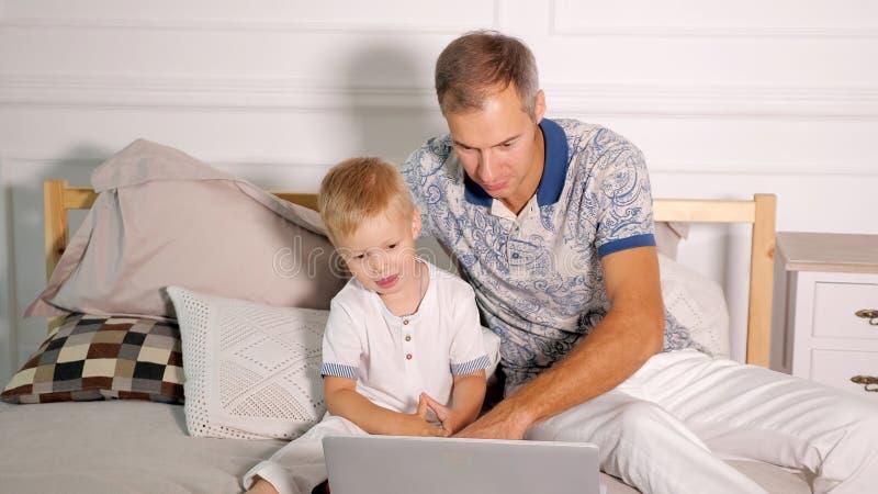 Mens met zoon het letten op laptop op bed royalty-vrije stock fotografie