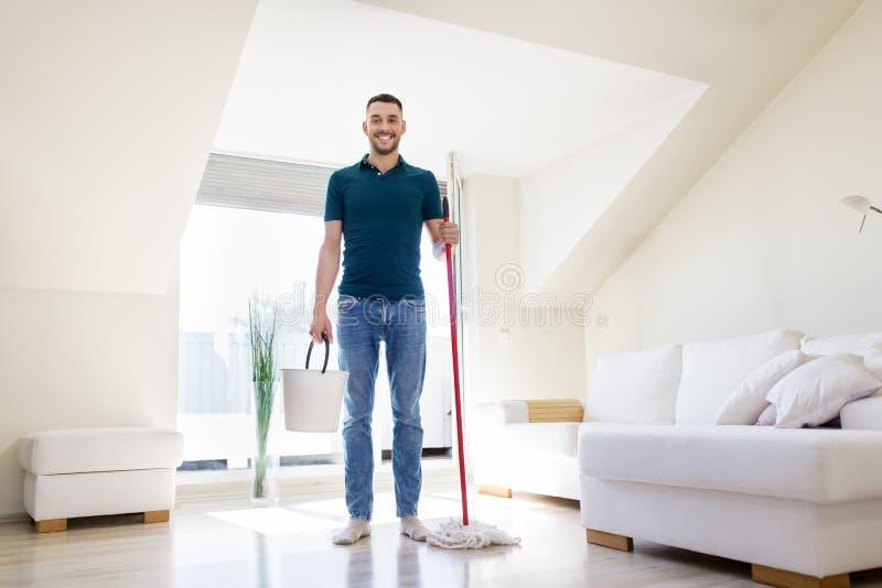 Mens met zwabber en emmer schoonmakende vloer thuis royalty-vrije stock fotografie