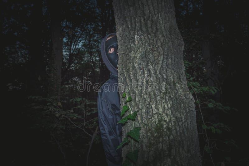 Mens met zwart masker in het hout stock foto
