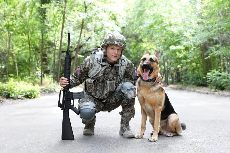Mens in militaire eenvormig met Duitse herderhond stock afbeeldingen