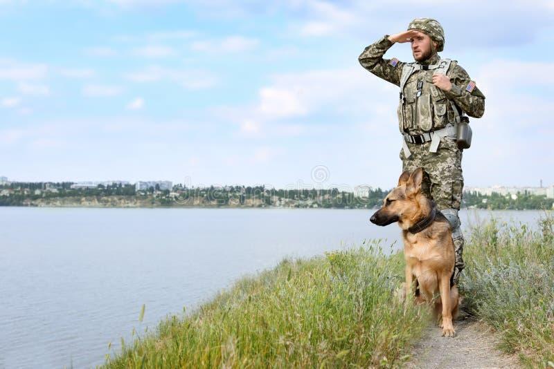 Mens in militaire eenvormig met Duitse herderhond in openlucht royalty-vrije stock foto
