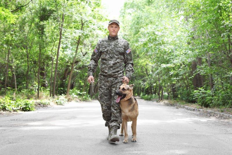 Mens in militaire eenvormig met hond, in openlucht royalty-vrije stock afbeeldingen
