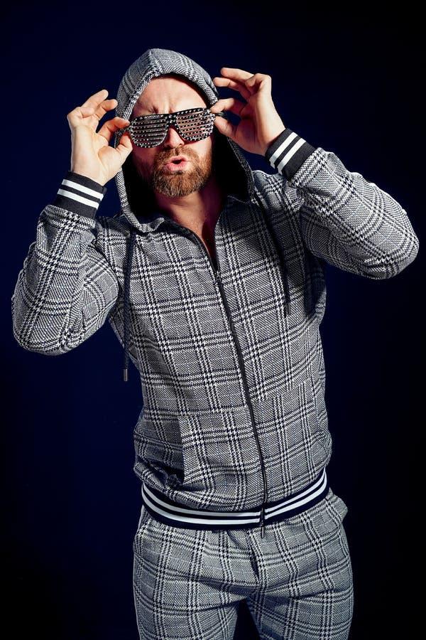 In mens in modieus sportkostuum en zonnebril stock fotografie