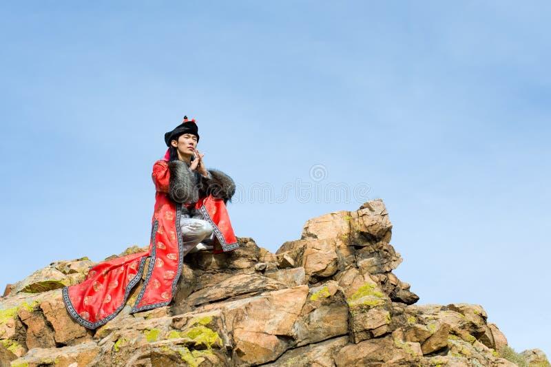 Mens in Mongools kostuum op rots royalty-vrije stock foto's