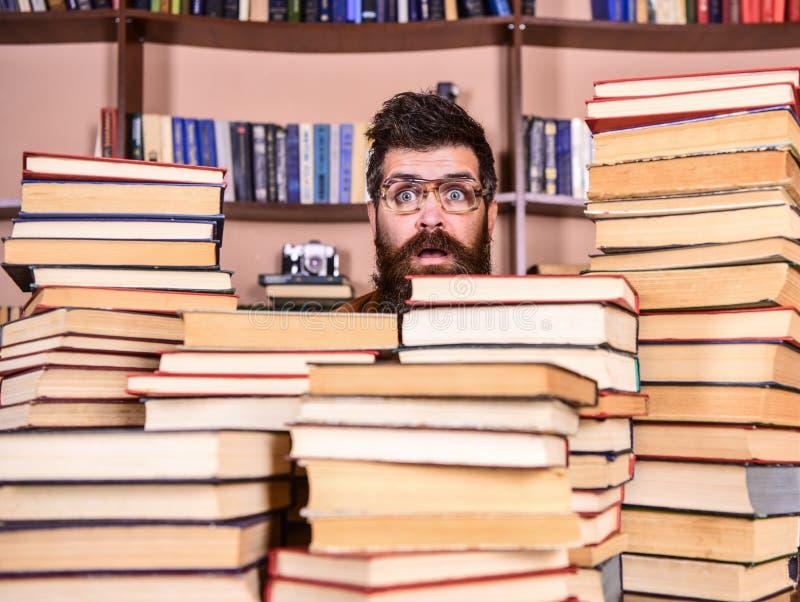 Mens, nerd op verrast gezicht tussen stapels van boeken in bibliotheek, boekenrekken op achtergrond Leraar of student met baard stock foto's