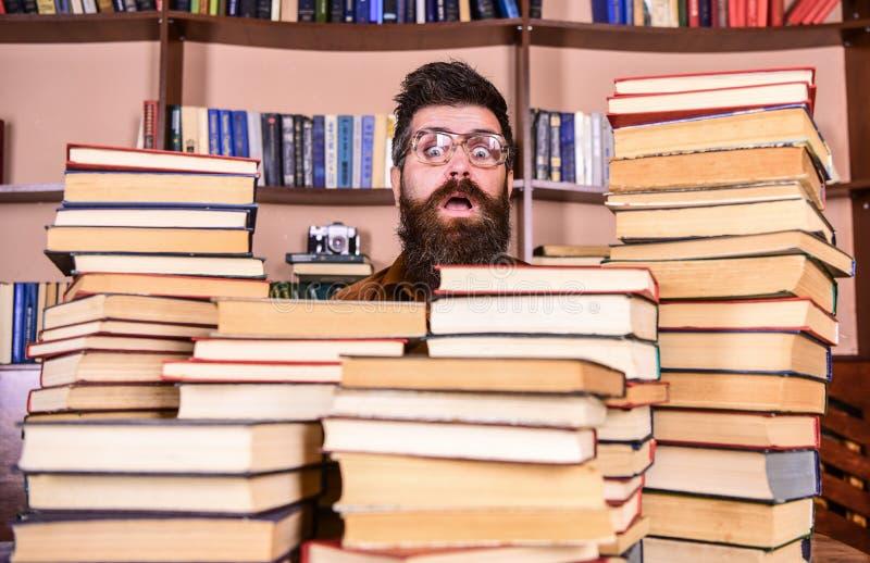 Mens, nerd op verrast gezicht tussen stapels van boeken in bibliotheek, boekenrekken op achtergrond Nerdconcept Leraar of royalty-vrije stock afbeelding