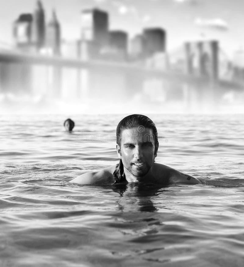 Mens in oceaan met stadsachtergrond stock fotografie