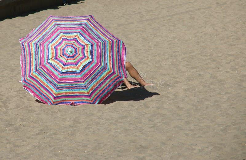 Mens onder een gestreepte strandparaplu royalty-vrije stock foto's