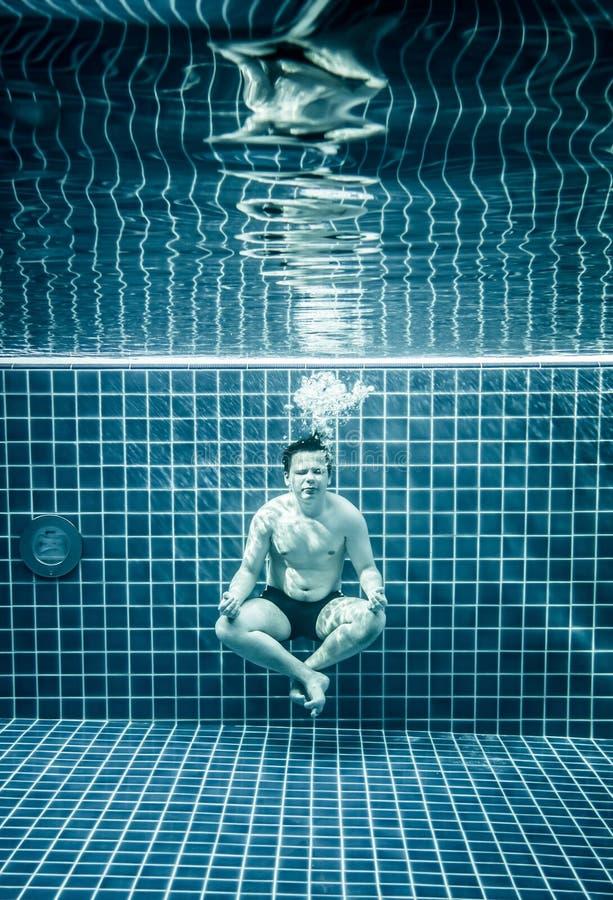 Mens onder water in een zwembad om in lotusbloempositio te ontspannen stock fotografie