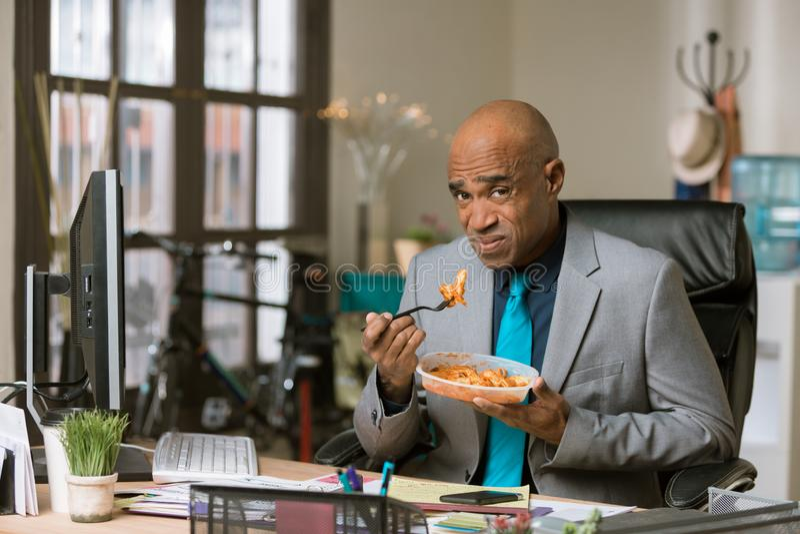 Mens Ongelukkig met Zijn Lunch op het Werk stock foto's