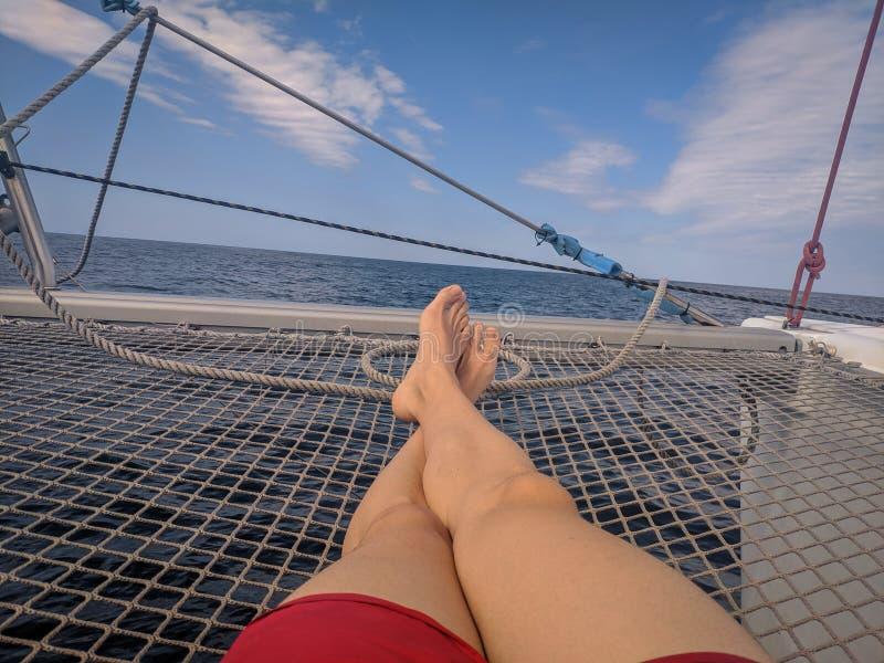 Mens ontspannen die in het net van een catamaran liggen stock afbeeldingen