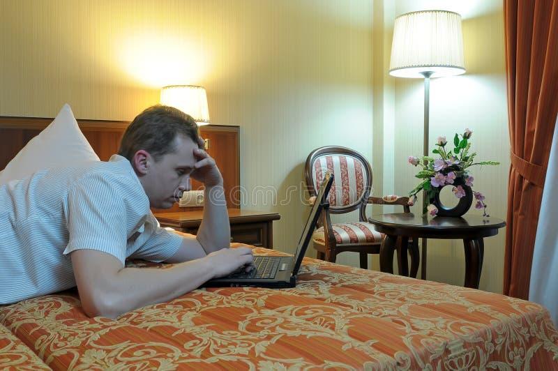 Mens op bed dat computer met behulp van stock foto