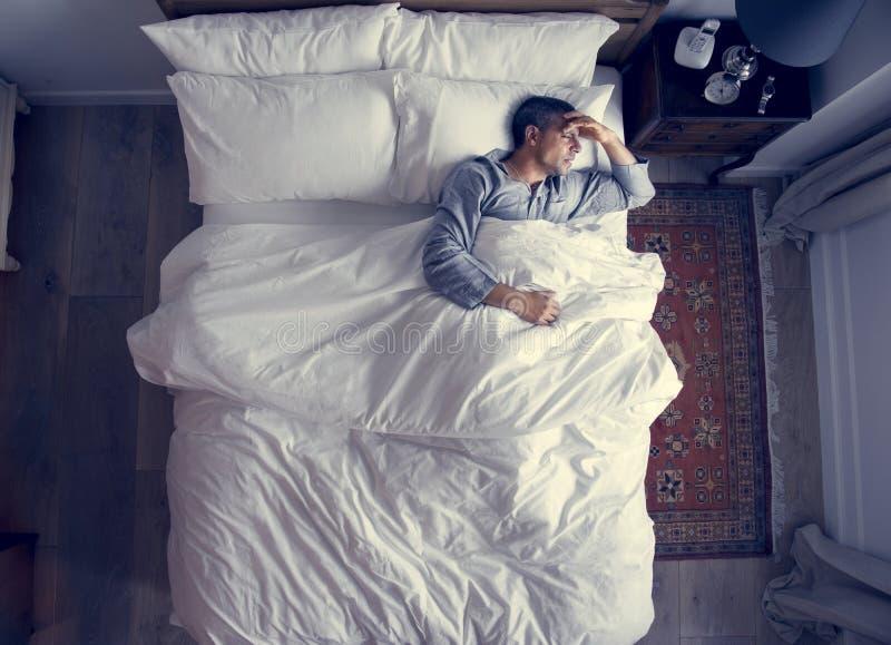 Mens op bed met een hoofdpijn stock afbeelding