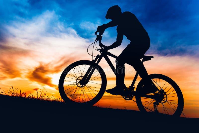 Mens op bergfiets bij zonsondergang, berijdende fiets op heuvels stock foto