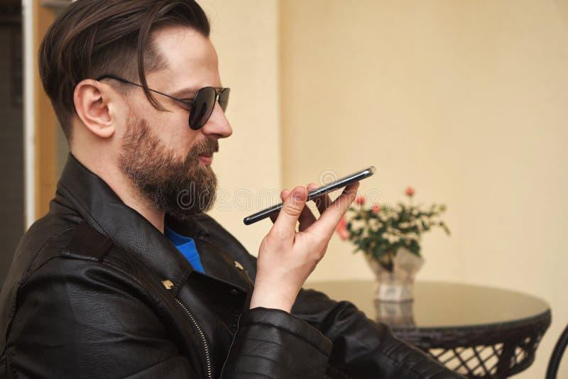 In mens op de koffie van het de zomerterras met smartphone stock afbeelding