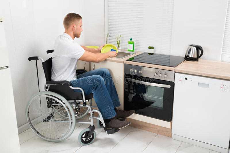 Mens op de schotels van de rolstoelwas stock afbeeldingen